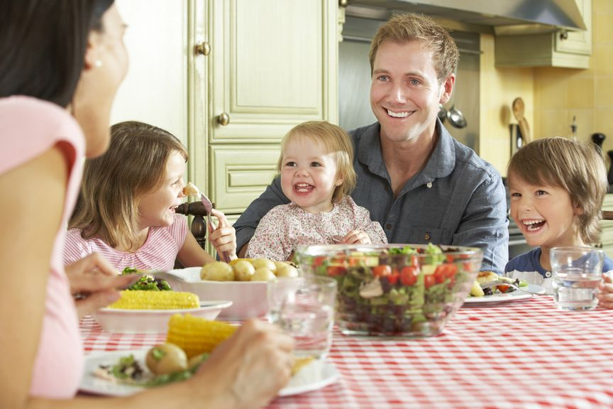 Familie sitzt am Esstisch bei einer Mahlzeit mit Salat und Gemüse