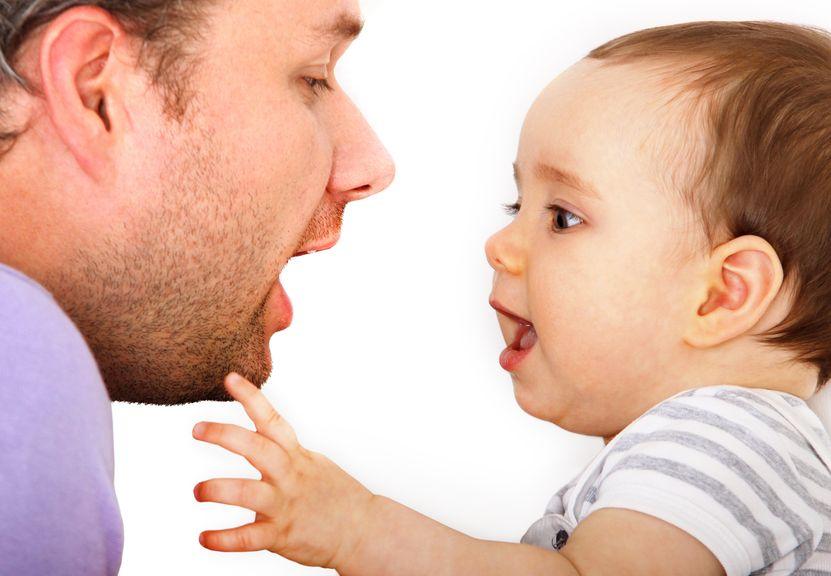 Vater und Baby sehen sich mit geöffnetem Mund an