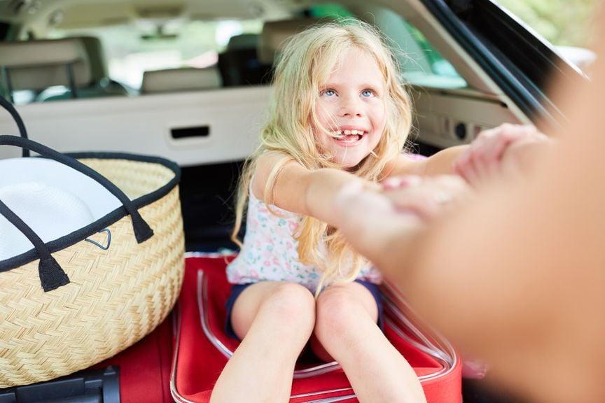 Mädchen sitzt im Kofferraum