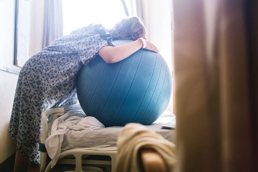 Gebärende lehnt über einen Fitnessball