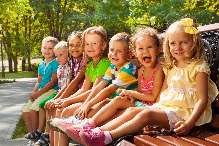 Kindergartenkinder machen Pause auf Parkbank