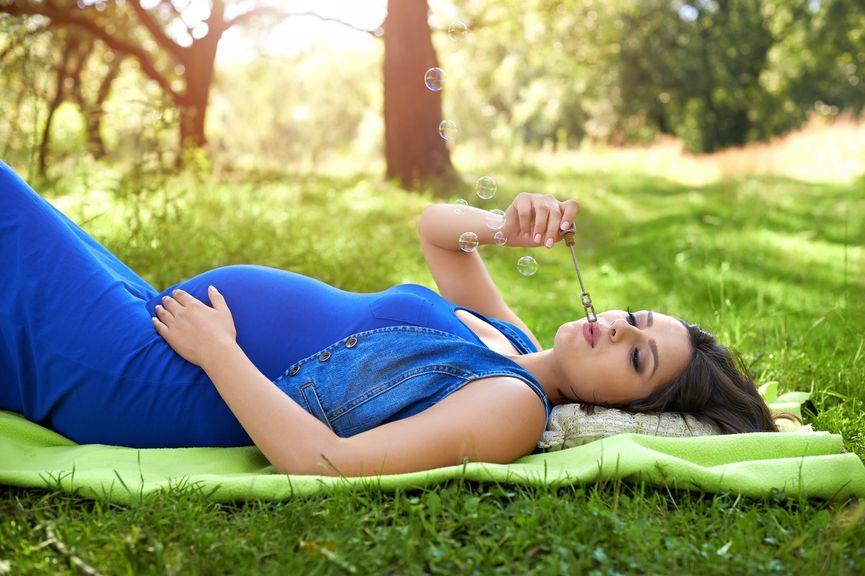 Schwangere entspannt sich auf der Wiese im Park
