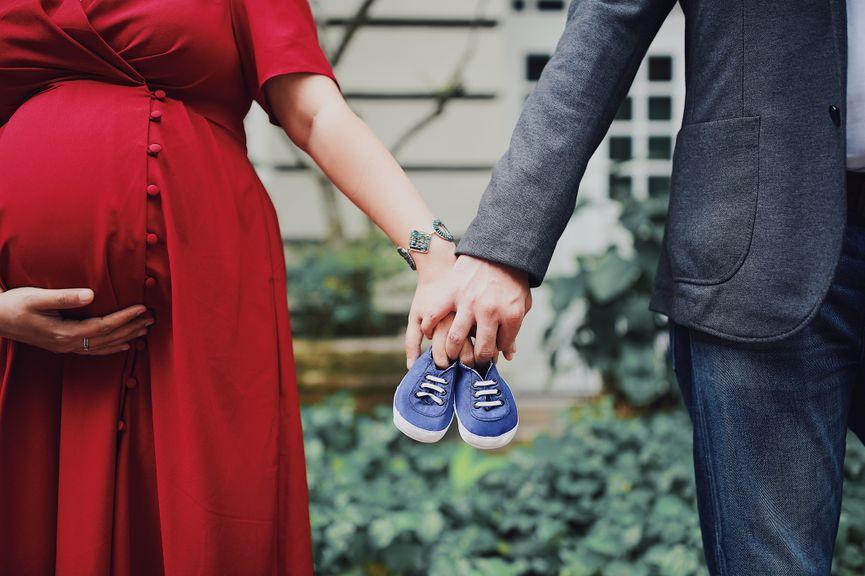 Schwangeres Paar hält sich an den Händen mit Babyschuhen