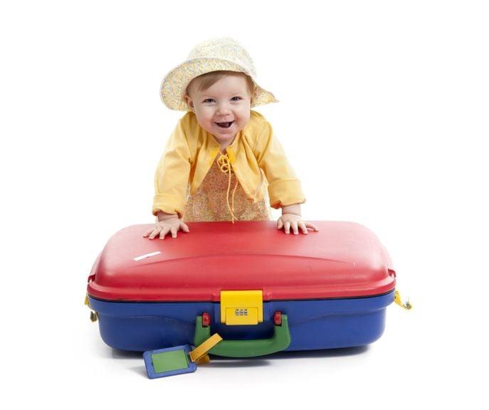 Kind steht am farbigen Koffer