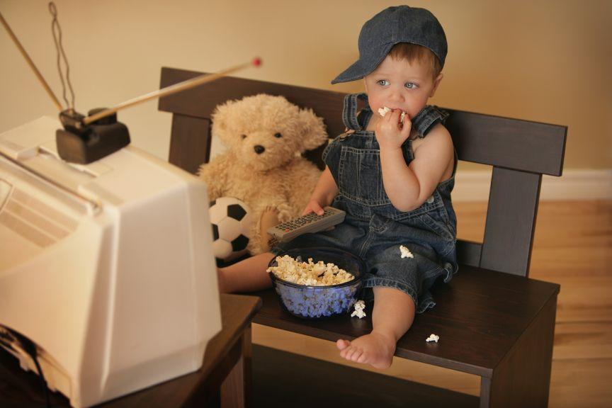 Kind mit Teddy vor dem Fernseher