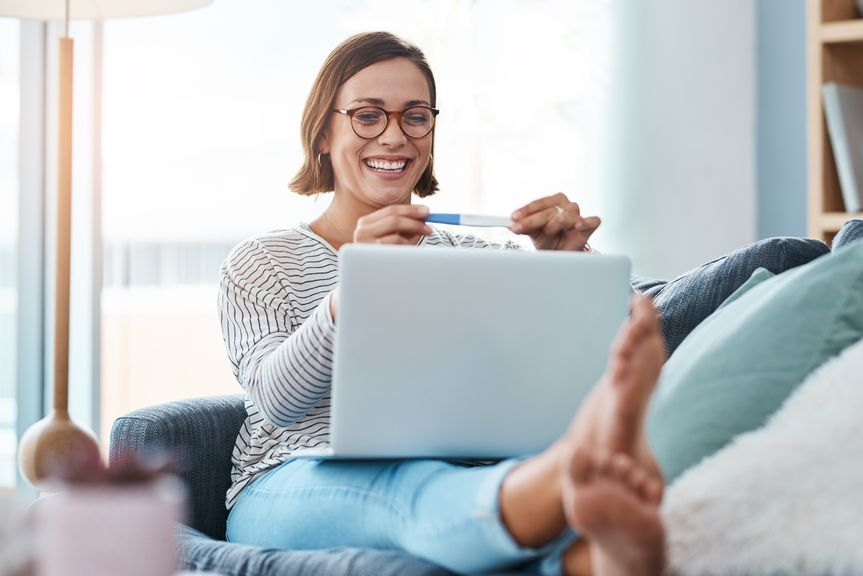 Frau mit Schwangerschaftstest und Laptop strahlt