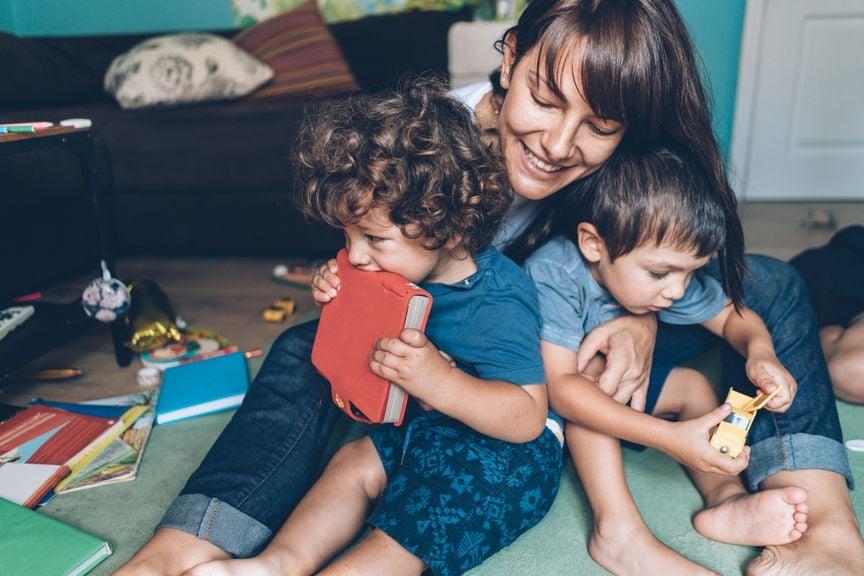 Glückliche Mutter mit zwei Kindern und Unordnung