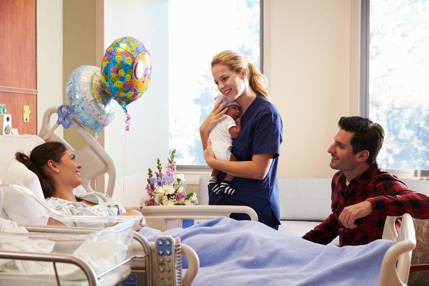 Schwester bring Neugeborenes der Mutter ans Spitalbett