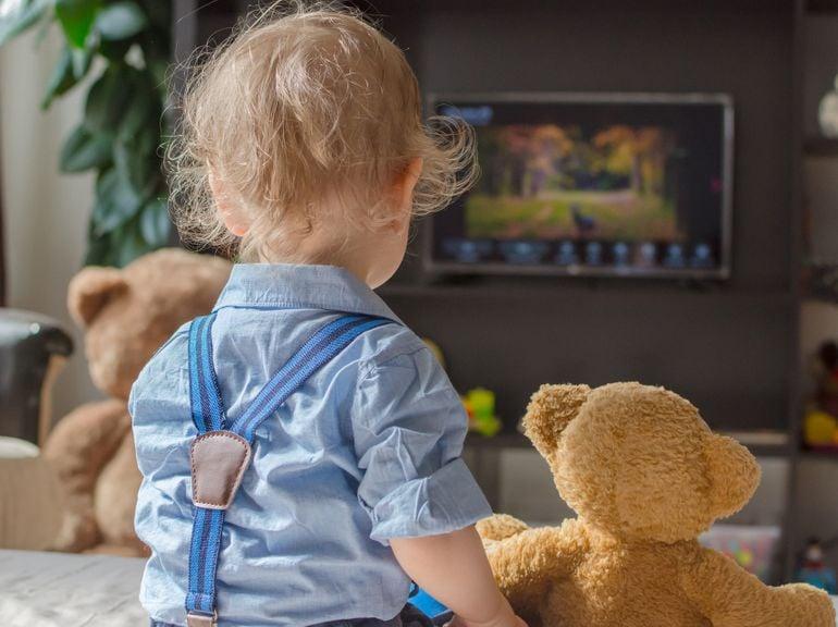 Kind sitzt mit Plüschtieren vor dem Fernseher