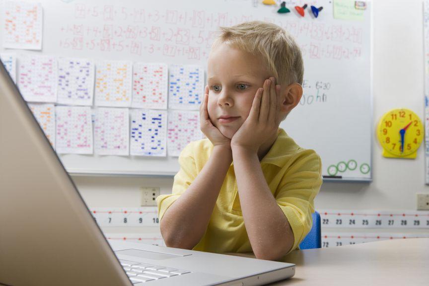 Kind im Klassenzimmer schaut auf den Laptop