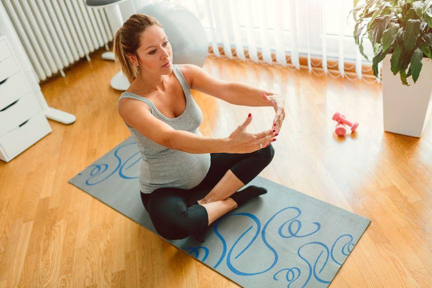Schwangere macht Yoga Übungen zu Hause