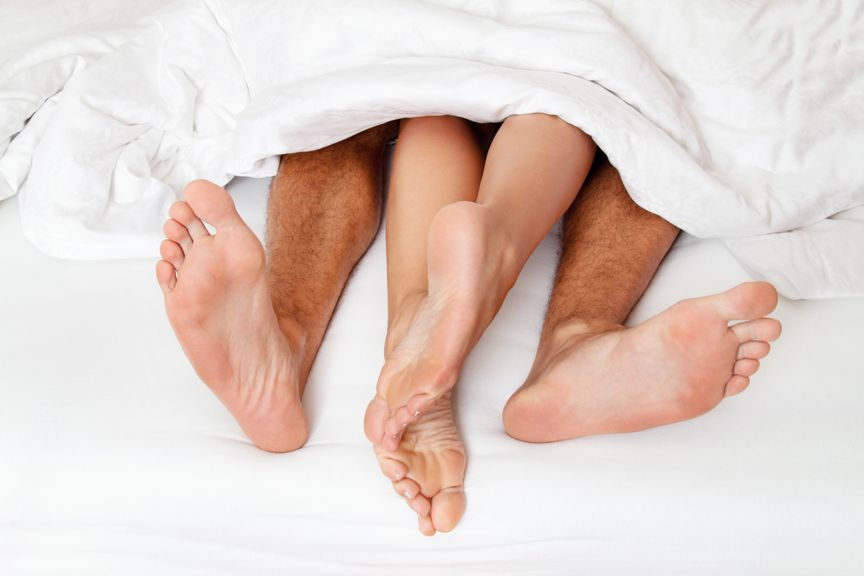 Paar im Bett, nur die Füsse unter der Bettdecke sichtbar