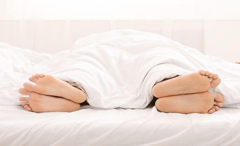 Füsse unter der Bettdecke, voneinander abgewandt
