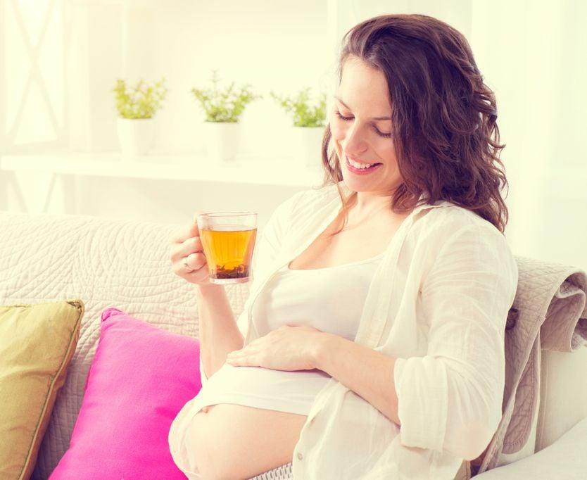 Schwangere sitzt auf dem Sofa und trinkt eine Tasse Tee