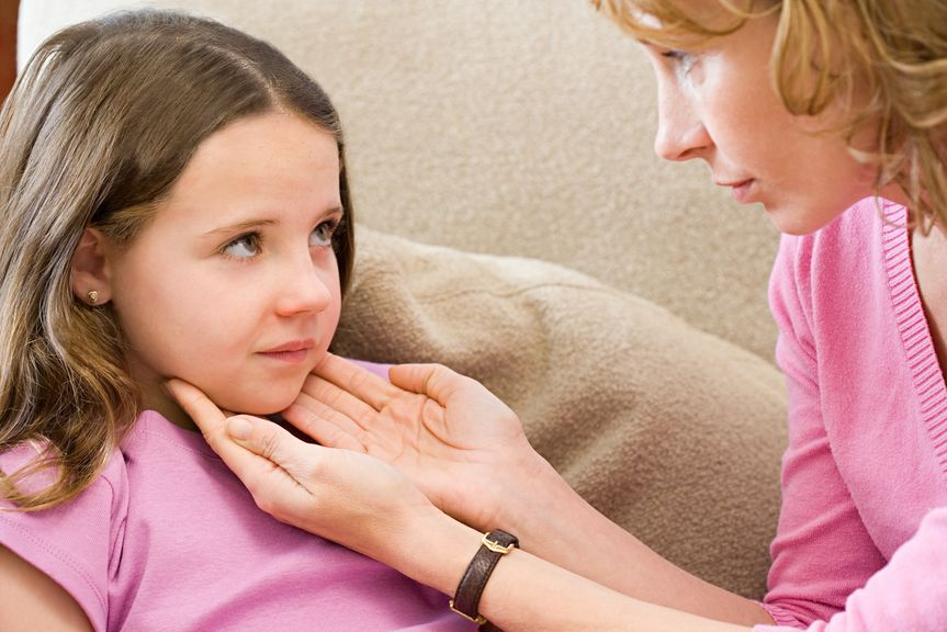 Mutter betastet die Halslymphknoten ihrer Tochter