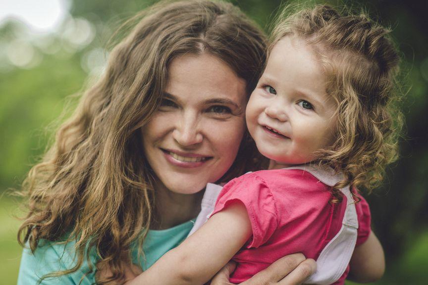 Strahlende Mutter mit Kind auf dem Arm