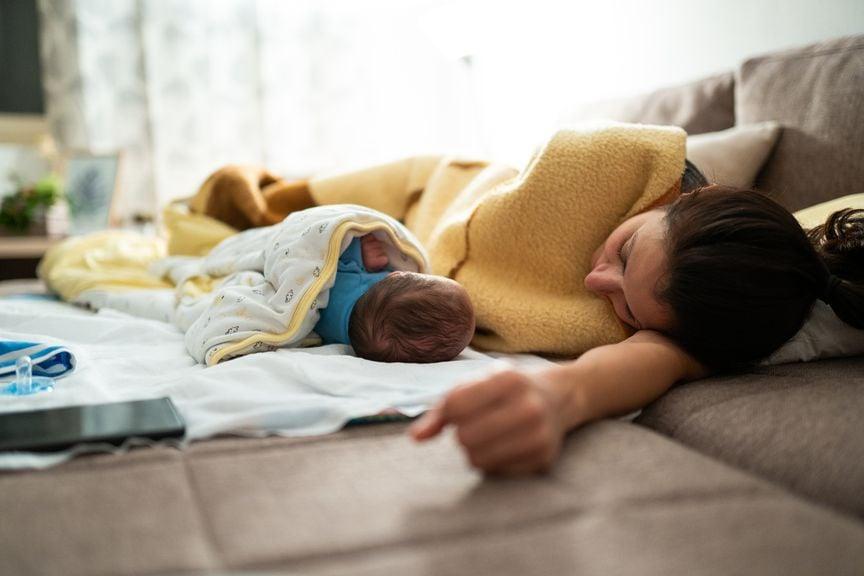 Erschöpfte Mutter ruht sich neben ihrem Neugeborenen aus