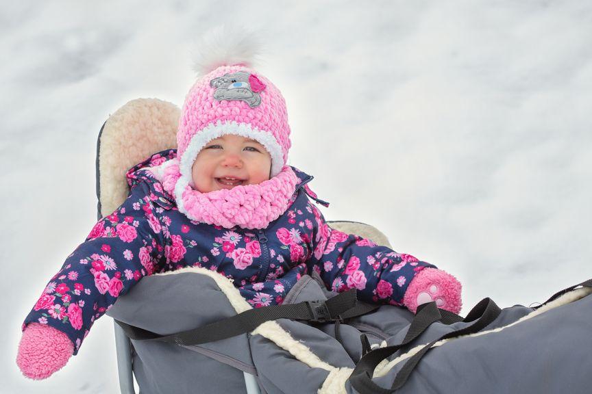 Baby warm verpackt auf dem Schlitten