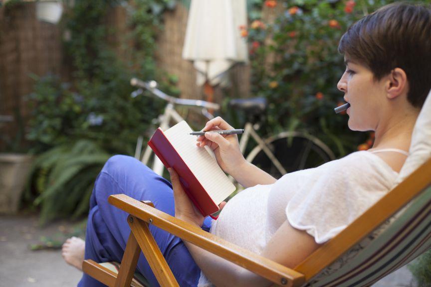 Schwangere im Liegestuhl schreibt Tagebuch