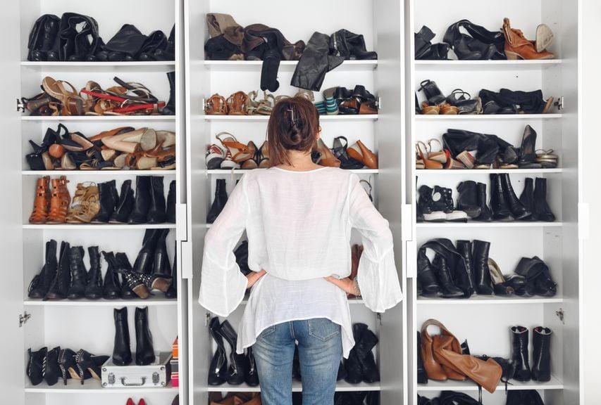 Frau vor überfülltem Schuhschrank