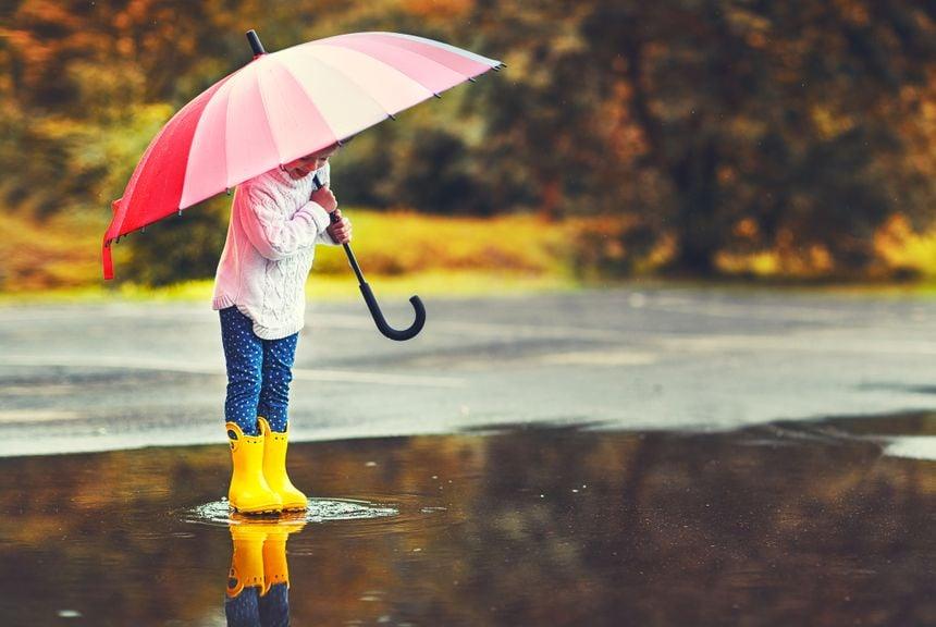 Mädchen steht mit Regenschirm und Gummistiefeln in grosser Pfütze