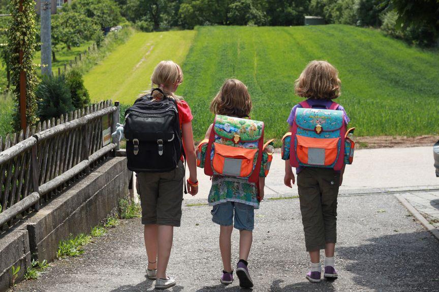 Kinder auf dem Schulweg, von hinten