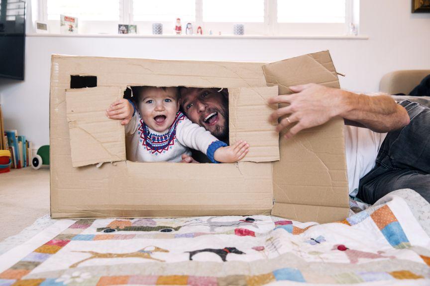 Kind und Vater im Haus aus Karton