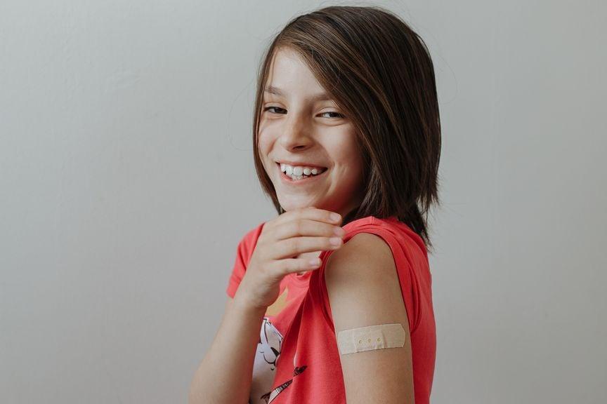 Teenager zeigt die Impfstelle