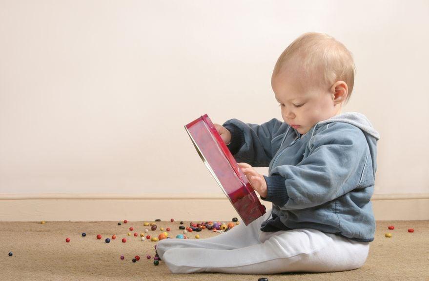 Baby mit einer Box bunter Plastikperlen