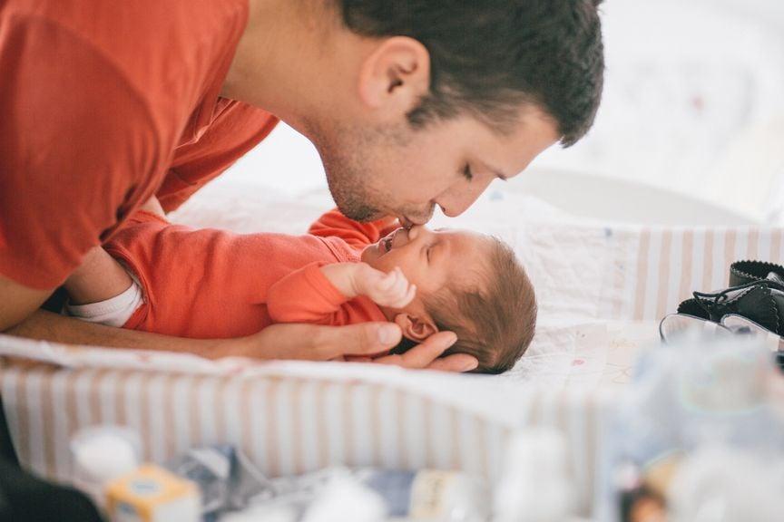 Vater wickelt neugeborenes Baby