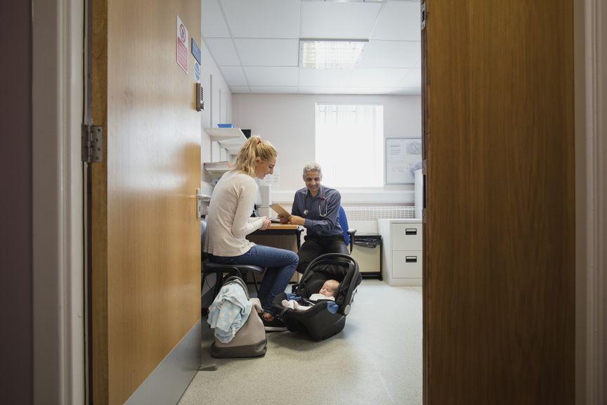 Mutter mit Baby in der Trage beim Arzt
