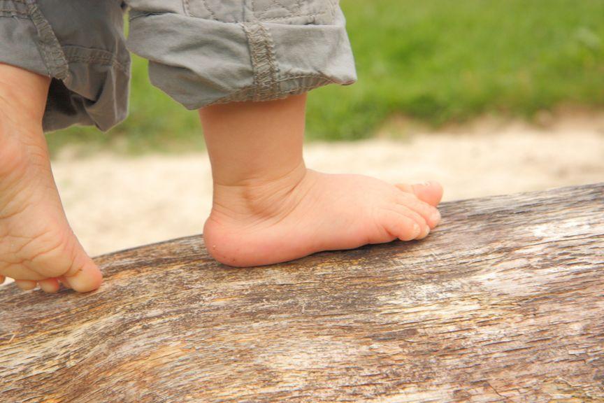 Nackte Kinderfüsse balancieren auf Baumstamm