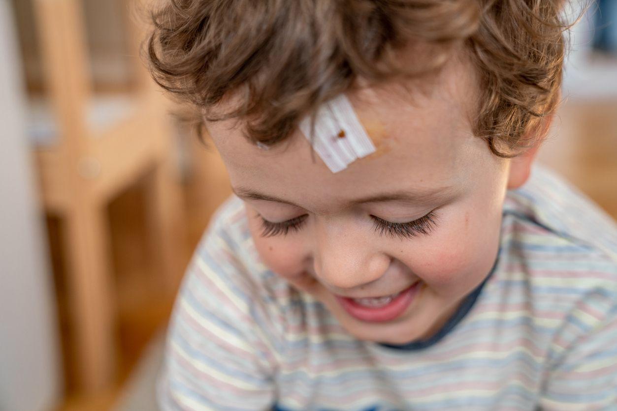 Kind mit behandelter Wunde am der Stirn