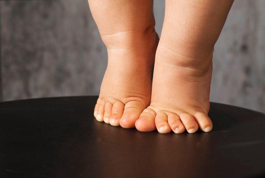 nackte Babyfüsse auf Zehenspitzen, nur die Füsse sichtbar