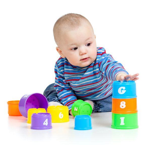 Baby türmt eine Becherpyramide aufeinander