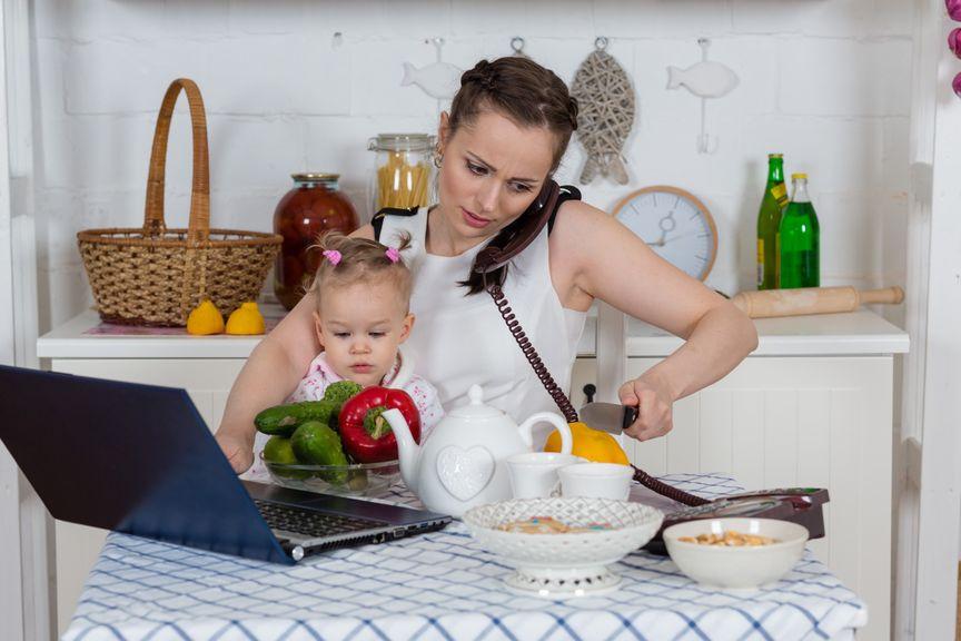 Mit Kind, Laptop und Telefon in der Küche