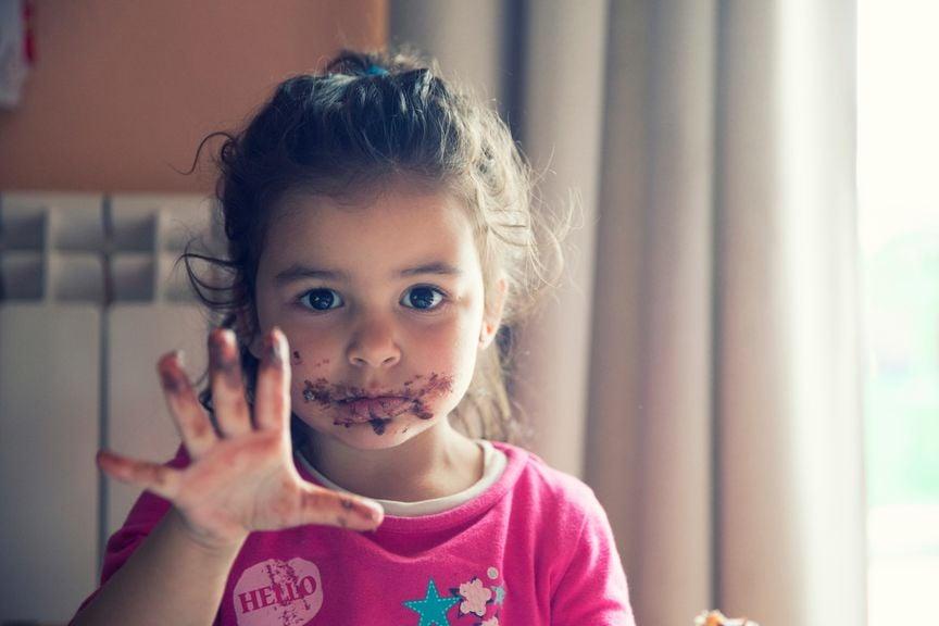 Mädchen mit Schoggi an Mund und Fingern