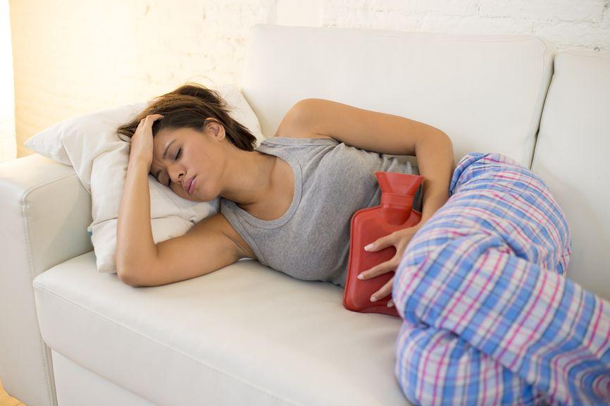 Frau mit Bauchschmerzen und Bettflasche