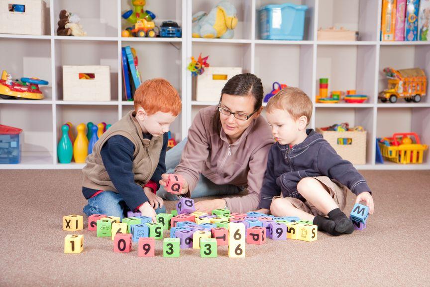 Betreuerin spielt mit Kindern am Boden
