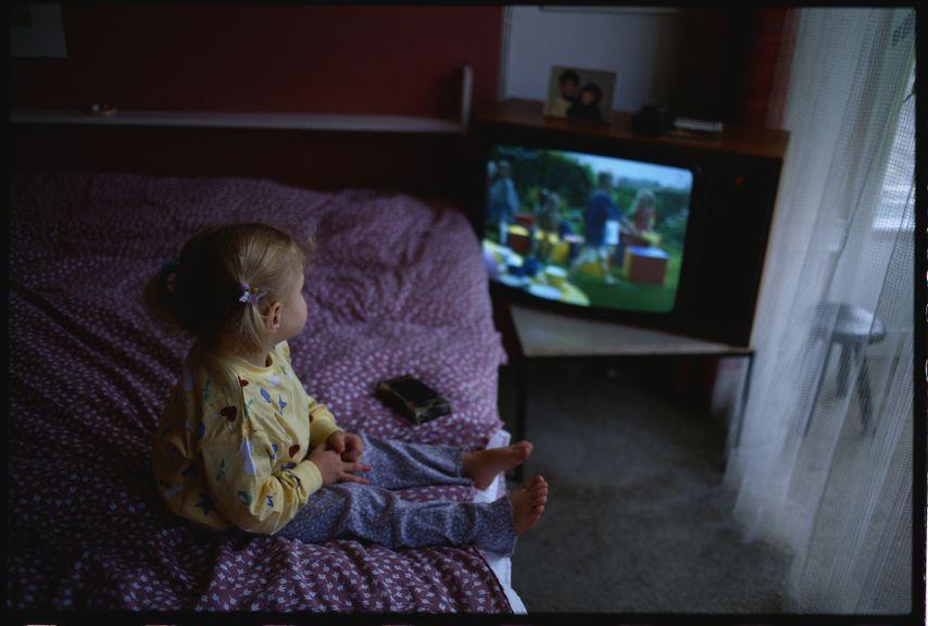 Kind im Pyjama sieht fern