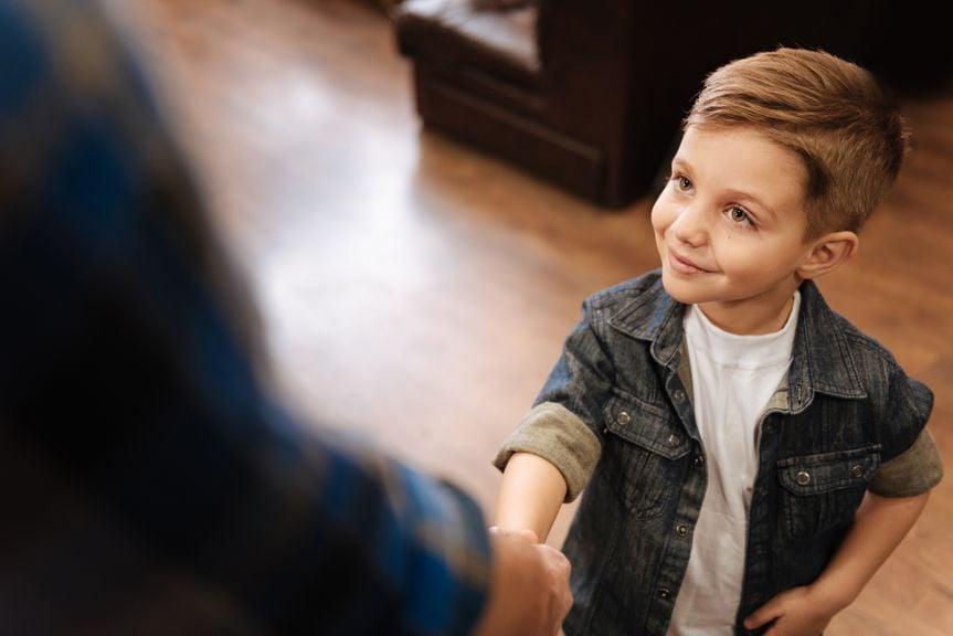 Freundlicher Junge gibt die Hand zur Begrüssung