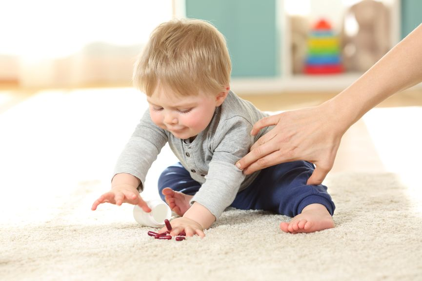 Hand der Mutter hält ein Kind zurück, das nach Tabletten greift,Kind greift nach Medikamenten am Boden
