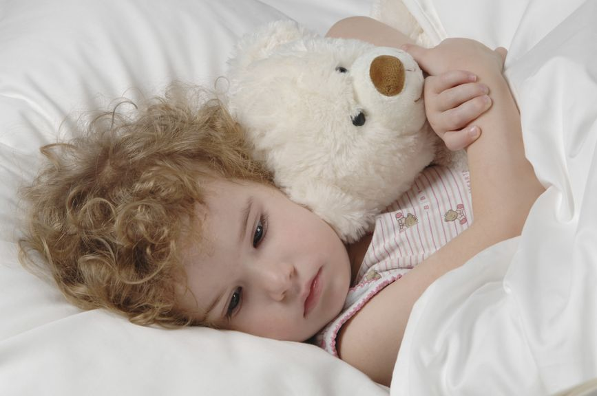 Kind mit Teddy im Bett