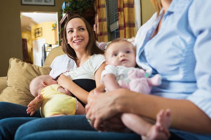 Stillende Mutter und Freundin mit Baby auf einer Couch sitzend