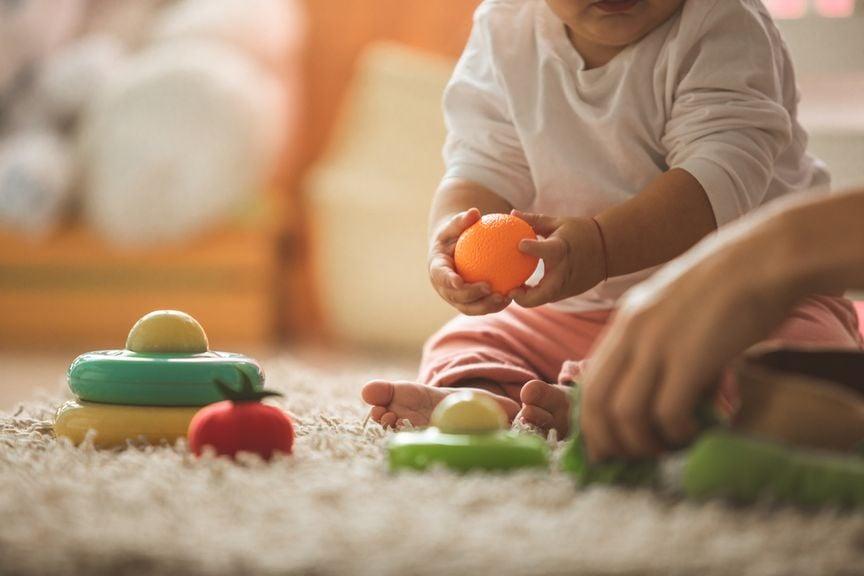 Baby sitzt auf dem Teppich und spielt