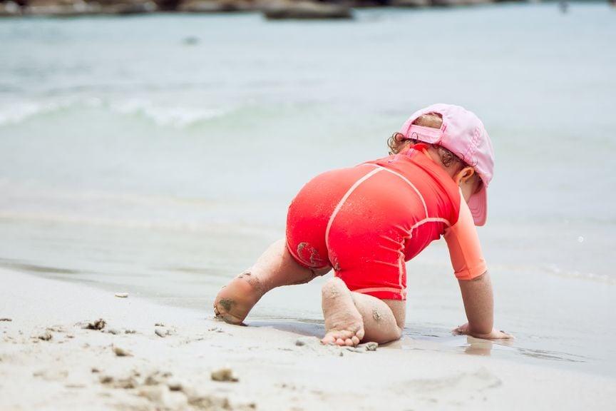 Kind am Strand, krabbelt zum Wasser