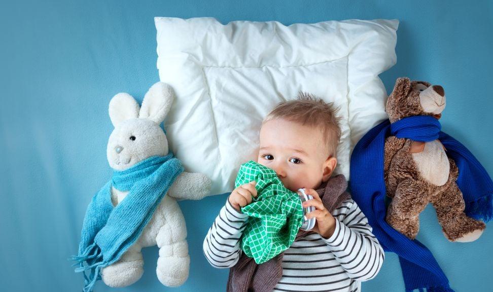 Baby mit Kuscheltuch und-tieren