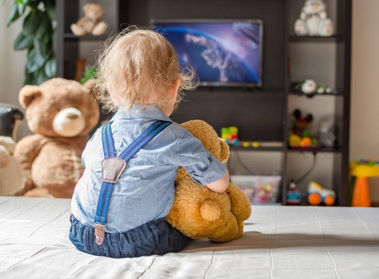 Kind mit Teddies vor dem Fernseher