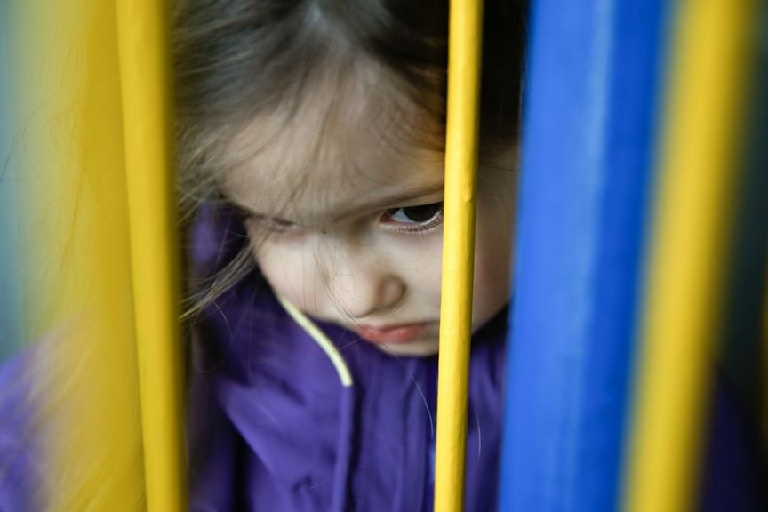 Mädchen schaut ängstlich und schüchtern durch eine Tür