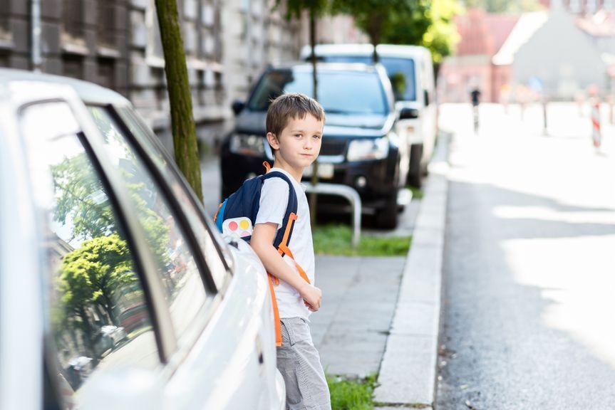 Junge hinter einem Auto möchte Strasse überqueren